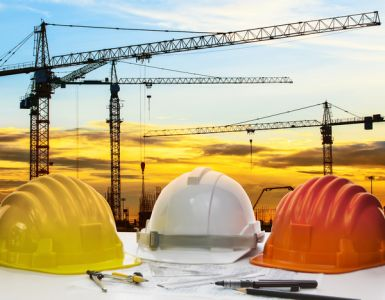 safety helmet and engineering plan with drawing instrument on engineer working table against crane construction and beautiful sun set scene use for construction and land development topic